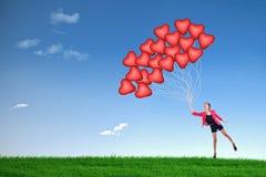 Ballons van het de greep de rode hart van het meisje stock afbeeldingen