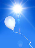 Balloon. Toy balloon soaring in the blue sky under shining sun Stock Images
