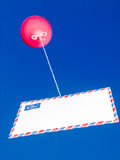 Balloon with airmail envelope. Red balloon attached to an airmail envelope by a string against a bright blue sky Stock Photo
