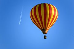 Balloon and an airplane on the blue sky Royalty Free Stock Photos
