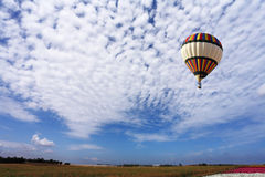 The  balloon with a basket flies by over fields Royalty Free Stock Photography