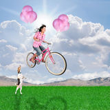 Balloon bike. A girl riding her balloon bike in the sky Stock Images