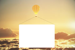 Balloon with blank advertising banner above the clouds at sunset Stock Images