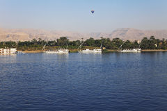 Balloon and boats on the Nile. Several white boat anchored on the banks of the Nile, the mountains in the distance and balloon flying Stock Photos