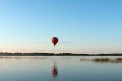 A balloon flies over the lake Royalty Free Stock Photo