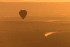 Balloon flies over truck in orange light royalty free stock photography