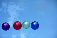 Balloon Floating in Swimming Pool. Four Color Balloon Floating in Swimming Pool.Color are Magenta,Red,Green and Dark Blue.The Water in Pool is Blue Color Stock Photo