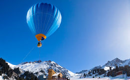 Balloon flying above mountain range at clear blue sky Royalty Free Stock Image