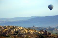 Balloon is flying in mountainous area in Cappadocia. Turkey Stock Photo
