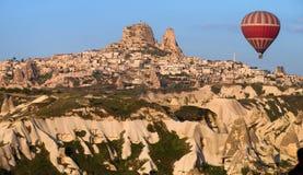 Balloon flying near the Uchisar Castle in Cappadocia, Turkey stock photography