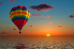 Balloon flying into sunset. Over water Stock Photo