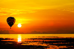 Balloon flying into sunset over the sea. Royalty Free Stock Photo
