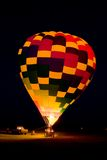 Balloon Glow. A hot air balloon team is lighting the balloon's propane burner while its tethered to the ground at night to produce a balloon glow Stock Photo