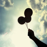 Balloon in hand under sun Royalty Free Stock Photos