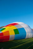 Balloon Hill. Colorful air balloon inflating on green grass Royalty Free Stock Photos