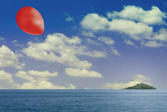 Balloon island escape. Red balloon floats above calm, sunny sea. Green island in the distance Stock Photography