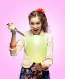 Balloon killer. Crazy girl is going to pop a balloon with a knife Stock Photos