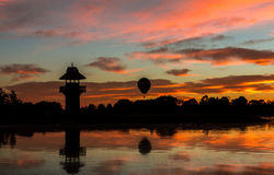 Balloon Lake Sunrise. Tower of Henley Lake at Masterton, New Zealand as the sun lights the morning sky. With a hot air balloon lifting off Royalty Free Stock Photos