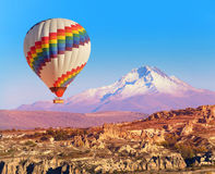 Balloon over Cappadocia. Balloon flying over rock landscape at Cappadocia Turkey with Erciyes Mountain Stock Photography