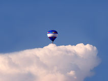 Balloon over a cloud. A colorful hot air balloon over a white sky in the blue sky Stock Photo