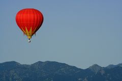Balloon Over the Mountains. A brightly colored hot air balloon floats in front of a mountain ranige Stock Photography