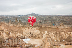 Balloon over rocky landscape of Cappadocia Valley at cloudy weather Royalty Free Stock Photography