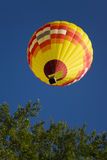 Balloon overhead. Yellow hot air balloon passes over head Royalty Free Stock Image