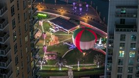 Balloon in park at Dubai Downtown night timelapse. Aerial view between two modern towers from above, United Arab Emirates. People walking near music fountain stock footage