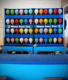 Balloon Pop Carnival Game. A bright blue carnival stand with a rainbow of multi colored balloons for players to pop with a darts for a prize royalty free stock photo