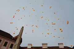 Balloon release of white and orange balloon next to church - Wish cards royalty free stock photos