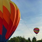 Balloon on the rise. A colorful Hot Air Balloon is ready to ascend while another brightly colored balloon floats by on a sunny Central Oregon morning Royalty Free Stock Photography