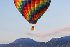 Balloon Rising in the Rockies. Hot air balloon taking off in front of the Rocky Mountains Royalty Free Stock Photo
