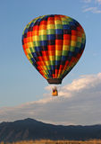 Balloon Rising in the Rockies. Hot air balloon taking off in front of the Rocky Mountains Royalty Free Stock Image