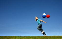 Balloon Run. Young boy running with brightly coloured balloons royalty free stock images
