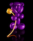 Balloon sculpture of a bear with a golden flower Stock Images