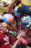 Balloon seller holding colorful balloons Stock Photos