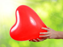 Balloon in the shape heart in hands Royalty Free Stock Images