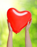 Balloon in the shape heart in hands Stock Photo