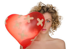 Balloon in shape of heart and hurt woman Royalty Free Stock Photography