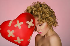 Balloon in shape of heart and hurt young woman Royalty Free Stock Photography
