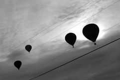 Balloon 'song'. Silhouettes of back-lit hot air balloons in dramatic evening sky behind electrical power lines, appearing as musical notes on a scale Stock Photo