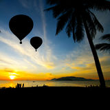 Balloon on Tropical beach with people in silhouette Stock Photography