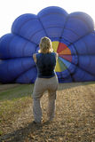 Balloonist inflating balloon. Balloonist inflating her blue balloon stock images
