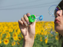 Balloons. Young blonde girl blowing water balloons Stock Photography