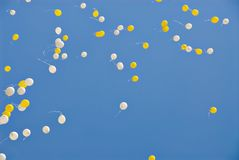 Balloons. White and yellow balloons flying up into the blue sky Stock Image