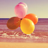 Balloons in the beach with a retro effect. Picture of a bunch of balloons of different colors flying in the sky over the ocean, with a retro effect Royalty Free Stock Photo