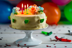 Balloons and birthday cake with candles for a party Stock Images