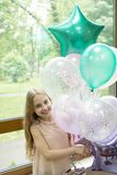 Balloons and birthday tunes. Happy cute little girl celebrating holiday with party balloons. Adorable small child. Smiling with bunch of air balloons. Helium stock photography