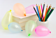 Balloons, books and pencils on a white background Stock Photography
