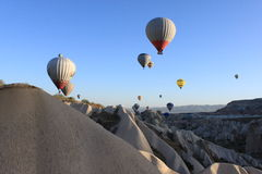 Balloons in Cappadocia. Hot air balloons rise over the beautiful rock formations in Cappadocia, Turkey.  The area is known for its distinctive moon-like Stock Photography